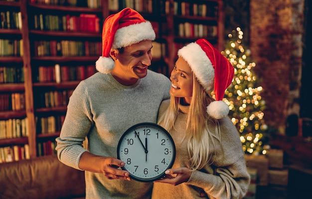 Vrolijk kerstfeest en een gelukkig nieuwjaar! jong koppel met klok in hun handen lachend vijf minuten tot het nieuwe jaar.