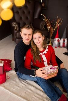 Vrolijk kerstfeest en een gelukkig nieuwjaar!. jong koppel vakantie vieren thuis. man en vrouw pakken geschenken uit