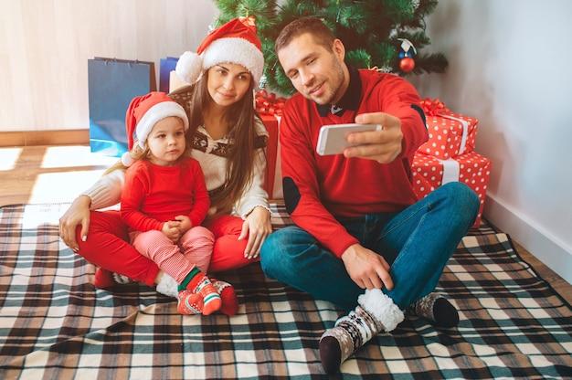 Vrolijk kerstfeest en een gelukkig nieuwjaar. jonge man zit naast vrouw en kind. hij houdt de telefoon vast en neemt selfie. vrouw en kind lok ernaar en poseren. familie draagt kerstkleding en hoeden.