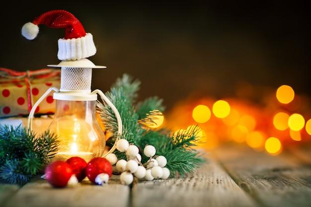 Vrolijk kerstfeest en een gelukkig nieuwjaar. kaars en kerstmisspeelgoed op een houten lijst op de lijst van een slinger. bokeh. selectieve aandacht. achtergrond