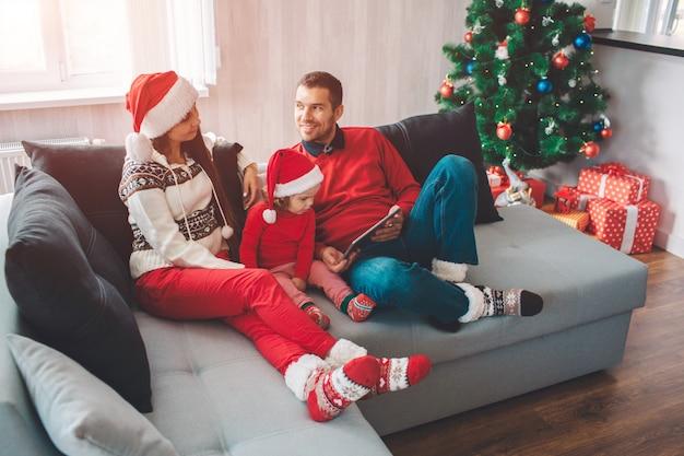 Vrolijk kerstfeest en een gelukkig nieuwjaar. kalme en vreedzame parenst die op bank met kind liggen. ze kijken elkaar aan. man lacht. hij houdt tablet. meisje kijkt ernaar.