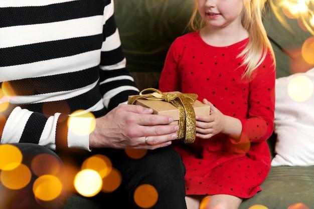 Vrolijk kerstfeest en een gelukkig nieuwjaar. kerstcadeau verrassing. dochtermeisje ontvangt kerstcadeau met verbazing. de vader geeft zijn dochter een geschenk bij de hand. geschenkdoos thuis binnen houden