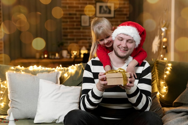 Vrolijk kerstfeest en een gelukkig nieuwjaar. kerstcadeau verrassing. een klein lachend dochtermeisje dat vader knuffelt en een cadeau binnenshuis vasthoudt, versierd voor vakantie. knappe man houdt geschenkdoos vast