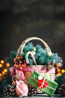 Vrolijk kerstfeest en een gelukkig nieuwjaar. mand met kerstmisspeelgoed en kerstmisgiften op een houten achtergrond.