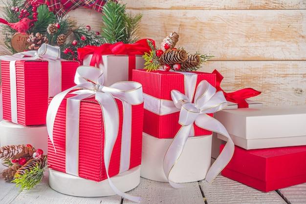 Vrolijk kerstfeest en een gelukkig nieuwjaar. noel wenskaart achtergrond. kerstgeschenkdozen met feestelijke linten, op trendy witte podia, met ruimte voor uw product, houten achtergrond