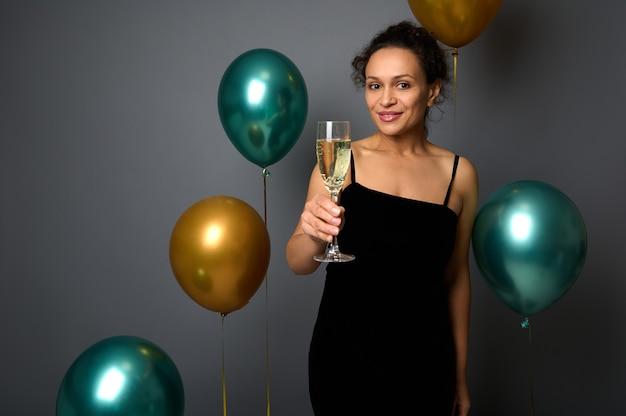 Vrolijk kerstfeest en een gelukkig nieuwjaar. promotie shot van mooie gemengd ras vrouw in avondjurk met glas champagne poseren tegen een grijze achtergrond met glanzende gouden en groene metalen ballonnen