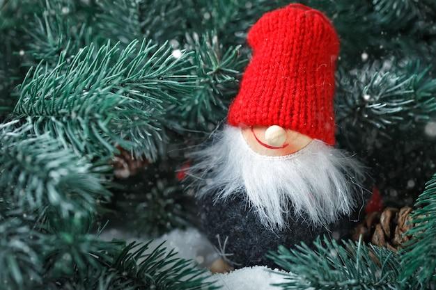 Vrolijk kerstfeest en een gelukkig nieuwjaar. toy santa in de takken van een spar. selectieve aandacht.