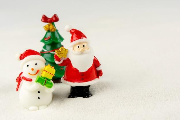 Vrolijk kerstfeest en een gelukkig nieuwjaarsconcept. leuke kerstman, sneeuwmancijfer en boom op sneeuw met exemplaarruimte