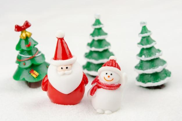 Vrolijk kerstfeest en een gelukkig nieuwjaarsconcept. leuke kerstman, sneeuwpopfiguur en boom op sneeuw met kopie ruimte