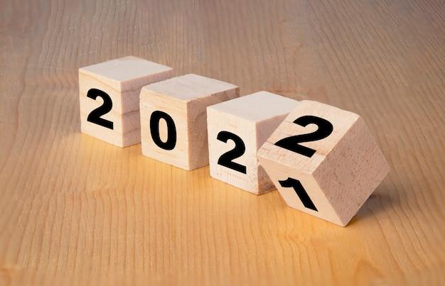 Vrolijk kerstfeest en een gelukkig nieuwjaarsconcept, omdraaien van de verandering van houten kubusblokken van 2021 tot 2022.