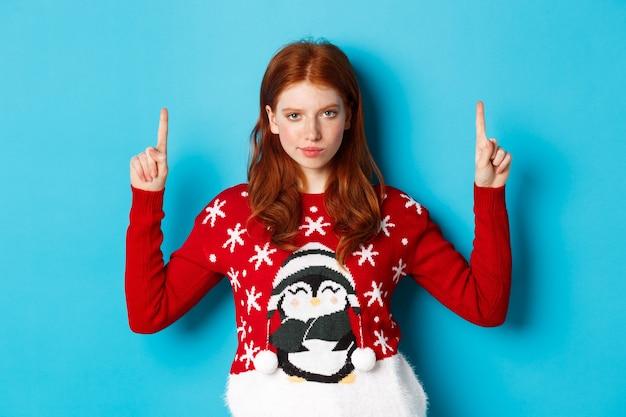 Vrolijk kerstfeest. ernstig en verdacht roodharig meisje dat naar de camera staart, vingers omhoog wijst naar een promo-aanbieding, staande in kersttrui tegen blauwe achtergrond.