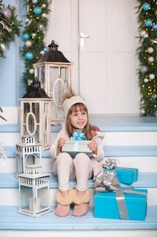 Vrolijk kerstfeest, fijne feestdagen! klein meisje zit met geschenken op de veranda van een huis ingericht voor kerstmis. kind zit op de veranda ingericht voor het oppervlak. kind opent kerstcadeau.
