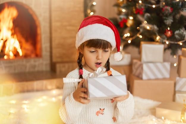 Vrolijk kerstfeest! gelukkig kind met geschenkdoos thuis in ingerichte woonkamer