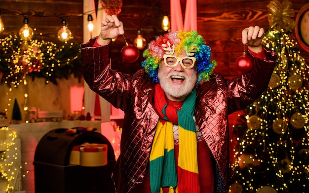 Vrolijk kerstfeest. gelukkig man met baard. volwassen bebaarde freak. kerstcadeaus. tijd voor cadeautjes. nieuwjaarsweekend. fanatieke vakantie. feestman in clownspruik. kerstboomversiering. gek worden.
