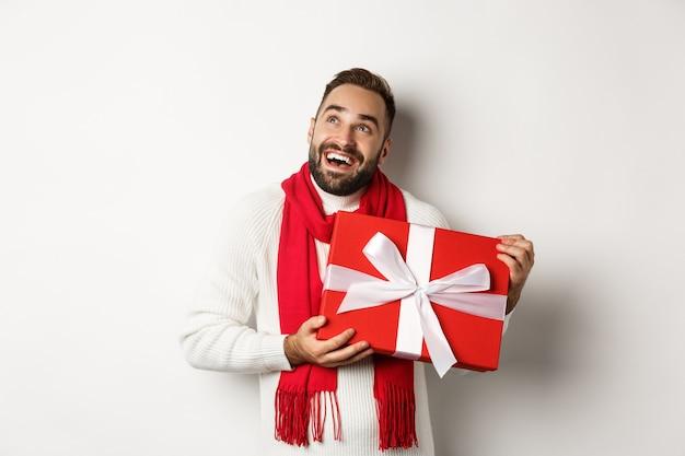 Vrolijk kerstfeest. gelukkige man die extatisch kijkt en zijn nieuwjaarscadeau vasthoudt, staande tegen een witte achtergrond.