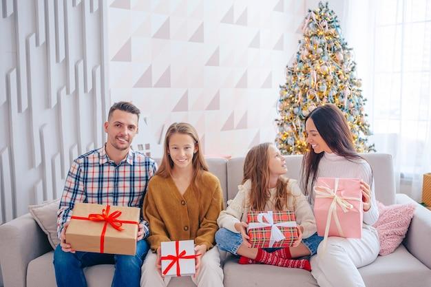 Vrolijk kerstfeest. gezin van vier met geschenken op kerstmis thuis