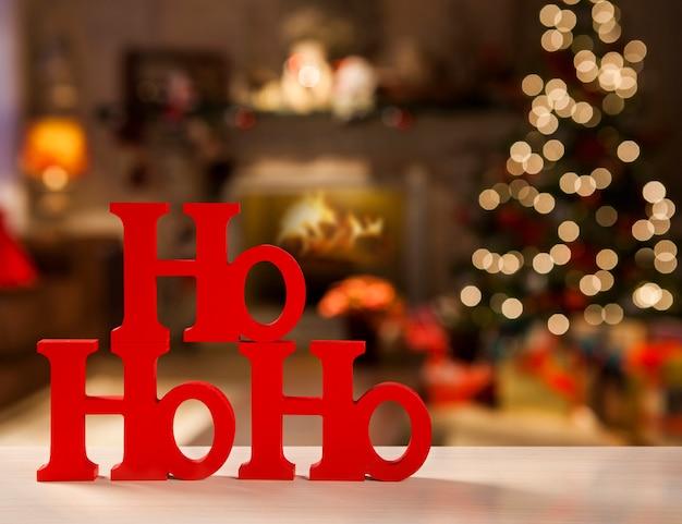 Vrolijk kerstfeest ho ho ho begroetingsbericht met kerstmis onscherpe lichte achtergrond.