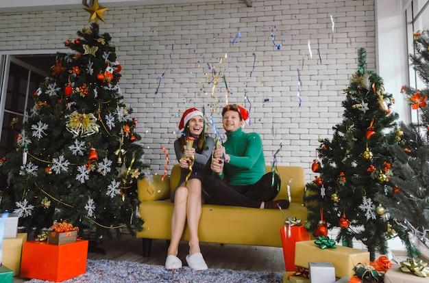Vrolijk kerstfeest. kaukasisch zoet paar met rode kerstmuts plezier met kleurrijke kerstboom vieren binnenshuis, vakantie familie, gelukkig nieuwjaar en kerstmis festival concept