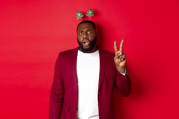 Vrolijk kerstfeest. mannelijke zwarte man in kostuum en dwaze feesthoofdband, vredesteken tonend maar serieus kijkend, staande over rode achtergrond.