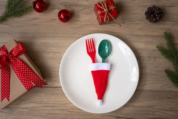 Vrolijk kerstfeest met bord, vork en lepel op houten tafel achtergrond. kerstmis, feest en gelukkig nieuwjaarsconcept