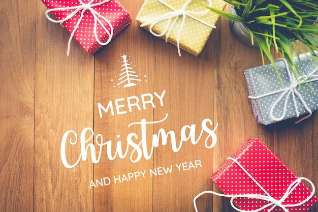 Vrolijk kerstfeest met leuke geschenkdoos presenteert op houten achtergrond