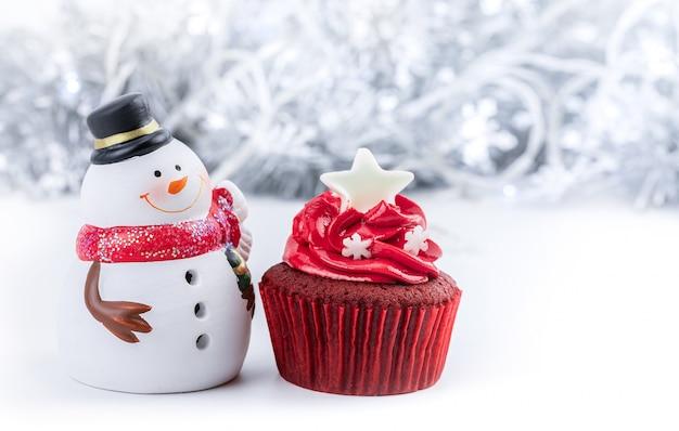 Vrolijk kerstfeest met rode cupcake en sneeuwpop