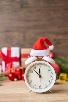 Vrolijk kerstfeest met vintage wekker en kerstversiering op houten tafel. feest, vakantie en tweede kerstdag concept