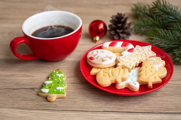 Vrolijk kerstfeest met zelfgemaakte koekjes en koffiekopje op houten tafel achtergrond. kerstavond, feest, vakantie en gelukkig nieuwjaarsconcept