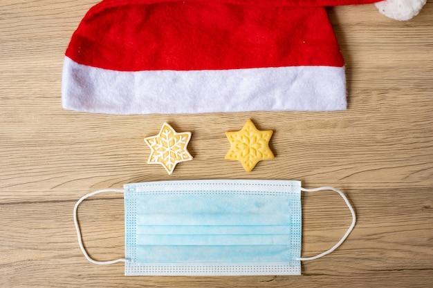 Vrolijk kerstfeest met zelfgemaakte koekjes, kerstman hoed en virusbeschermend gezichtsmasker op houten tafel achtergrond. gezondheid, covid 19 pandemie, kerstmis, feest, vakantie en gelukkig nieuwjaar concept