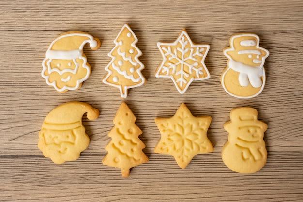 Vrolijk kerstfeest met zelfgemaakte koekjes op houten tafel achtergrond. kerstmis, feest, vakantie en gelukkig nieuwjaar concept