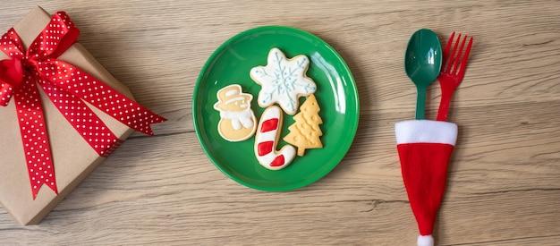 Vrolijk kerstfeest met zelfgemaakte koekjes, vork en lepel op houten tafel achtergrond. kerstmis, feest en gelukkig nieuwjaarsconcept