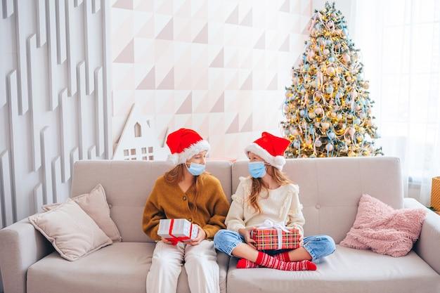 Vrolijk kerstfeest. mooie meisjes met geschenken op kerstmis. kinderen dragen gezichtsmaskers