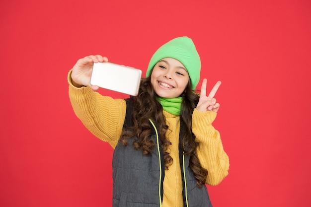 Vrolijk kerstfeest. nieuwjaar gefeliciteerd. gelukkig tienermeisje dat selfie met smartphone maakt. kerst winter online winkelen. mode voor het koude seizoen. kind in warme kleding. familie op vakantie bellen.