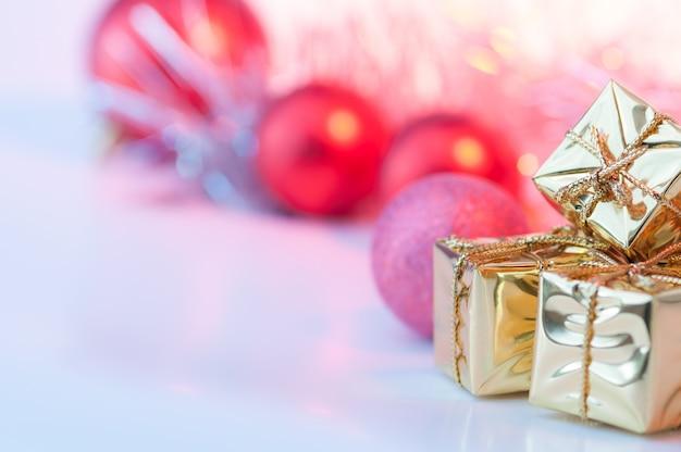 Vrolijk kerstfeest, nieuwjaar, geschenken in gouden dozen, rode kerstballen in de juiste hoek. achtergrond bokeh.