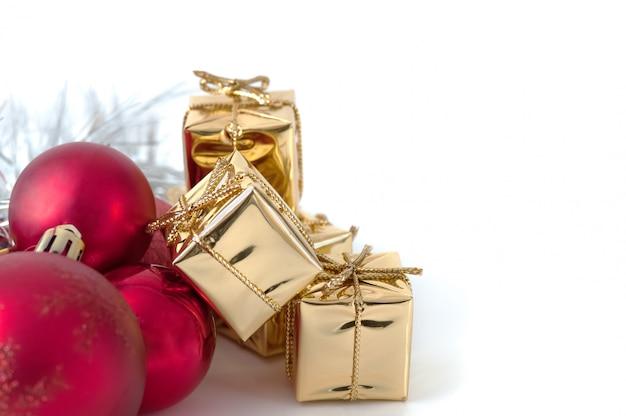 Vrolijk kerstfeest, nieuwjaar, geschenken in gouden dozen, rode kerstballen zijn opgestapeld in de linkerhoek. witte achtergrond.