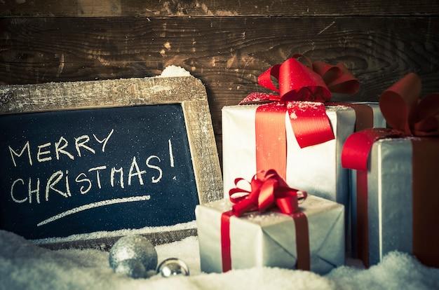 Vrolijk kerstfeest op een lei met geschenken.