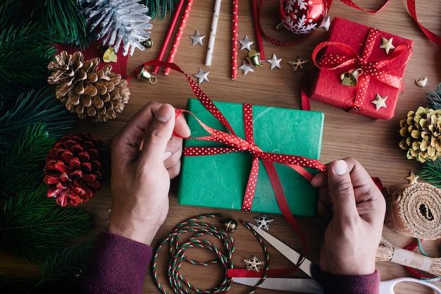 Vrolijk kerstfeest plat lag met menselijke hand versieren geschenkdoos aanwezig