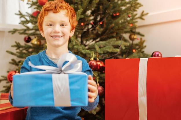 Vrolijk kerstfeest. schattige roodharige jongen met een vrolijke glimlach op zijn gezicht zittend op de grond en een kerstcadeau te geven.