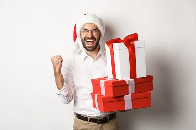 Vrolijk kerstfeest, vakantie concept. opgewonden man kerst geschenken ontvangen en vreugde, het dragen van kerstmuts, nieuwjaar, witte achtergrond vieren.