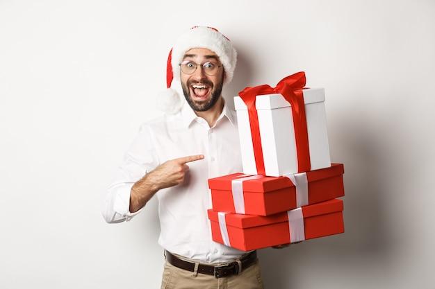Vrolijk kerstfeest, vakantie concept. verrast man ontvangt kerstcadeaus, wijzend op cadeautjes en glimlachend gelukkig, met kerstmuts, witte achtergrond.