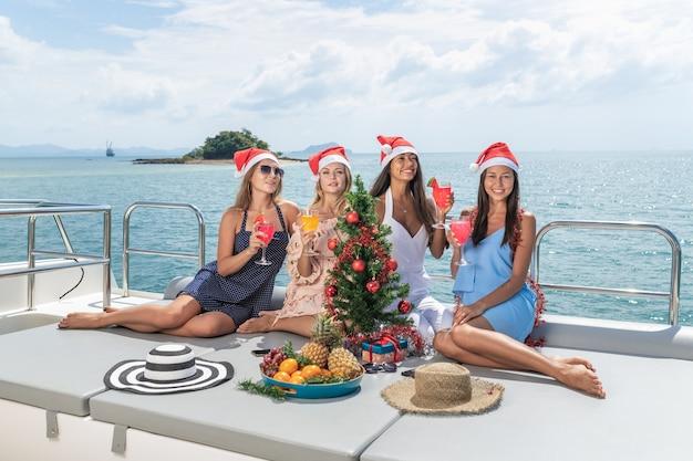 Vrolijk kerstfeest vier vriendinnen ontspannen zich op het jacht.