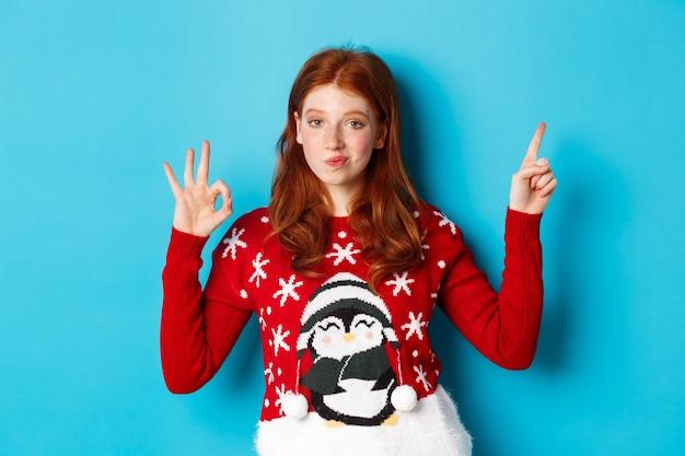 Vrolijk kerstfeest. vrolijk roodharig meisje in kersttrui, wijzende vinger in de rechterbovenhoek, met nieuwjaarspromo en oke bij goedkeuring, lofproduct.