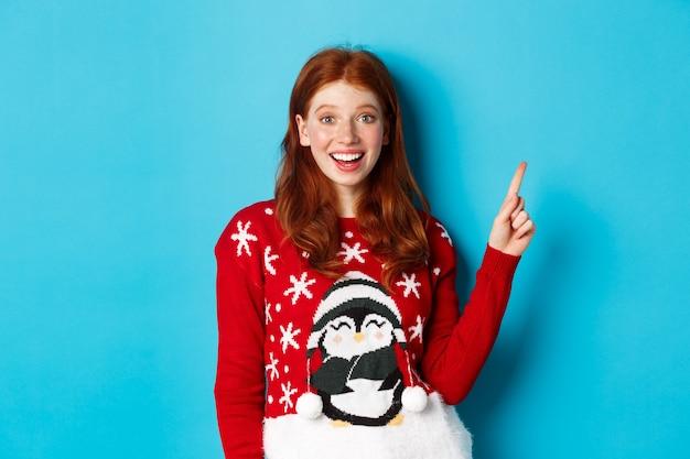 Vrolijk kerstfeest. vrolijk roodharig meisje in kersttrui, wijzende vinger naar de rechterbovenhoek en opgewonden glimlachend, met nieuwjaarspromo.