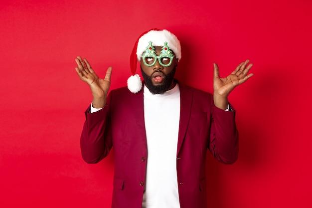 Vrolijk kerstfeest. vrolijke zwarte man met grappige partij bril en kerstmuts