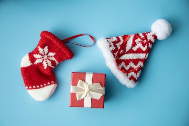 Vrolijk kerstmisconcept: rode doos huidige en rode baby pasgeboren sok en hoed op blauwe achtergrond