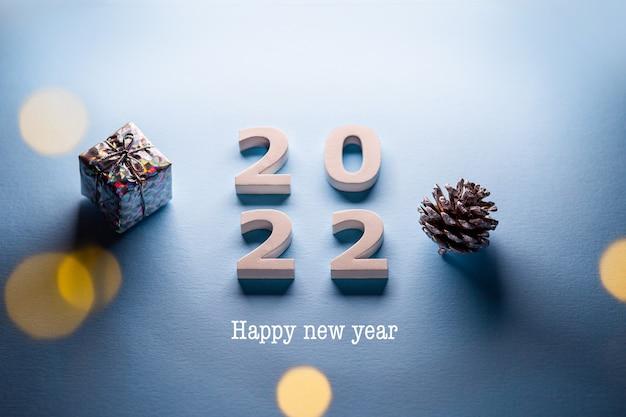 Vrolijk kerstthema gelukkig nieuwjaar 2022minimale kerstkaart op een blauwe achtergrond met een cadeau