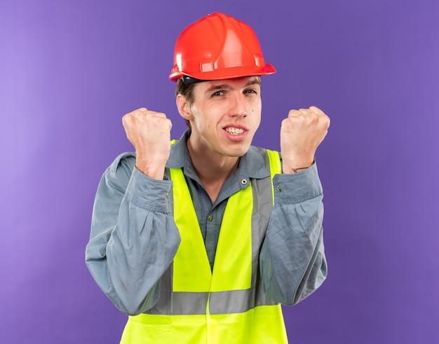 Vrolijk kijkend naar camera jonge bouwer man in uniform met ja gebaar