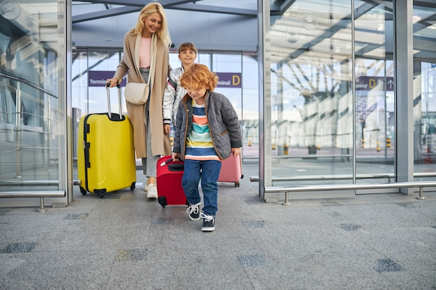 Vrolijk kind dat het vliegveld betreedt met zijn moeder en zus
