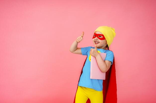 Vrolijk kind gekleed in superheld kostuum en een hoed met een boek in zijn handen.
