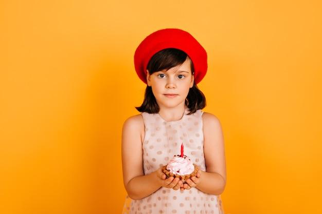 Vrolijk kind in franse baret die verjaardag viert. extatisch preteen meisje met cake geïsoleerd op gele muur.